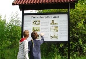 Tablica informacyjna przy dawnym wejściu na wzgórze pomnika.